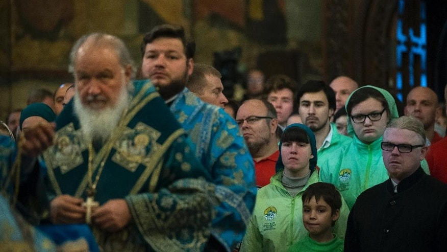 Believers wait as Russia's Patriarch Kirill prepares to conduct a religion service marking People's Unity Day inside the Cathedral of the Assumption, Cathedral Square in the Kremlin in Moscow, Wednesday, Nov. 4, 2015. The celebrations were scrapped in St. Petersburg as Russia's second-largest city mourns the victims of Saturday's plane crash in Egypt that killed 224 people. Authorities in Moscow, however, went ahead with the rally, which culminated in a pop concert on a central street.  (AP Photo/Alexander Zemlianichenko)