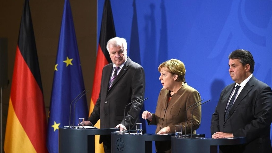 The heads of the German government's coalition parties, Chancellor Angela  Merkel of the Christian Democratic Union party, center, Bavarian governor  Horst Seehofer of  the Christian Social Union party, left , and vice chancellor Sigmar Gabriel of the Social Democrats, right, give a short press statement regarding their negotiations on refugee policy ,  in Berlin Thursday Nov. 5, 2015.  ( Bernd von Jutrczenka/dpa via AP)