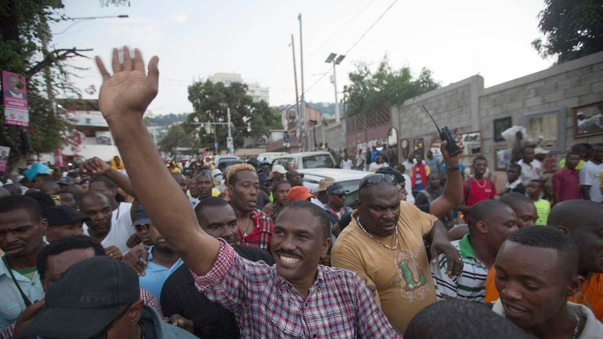 FILE - in this Oct. 22, 2015 file photo, Presidential candidate Jude Celestin from the LAPEH political party, waves to supporters during a rally in Petion-Ville, Port-au-Prince, Haiti.  Electoral authorities say on Thursday, Nov. 5, 2015, Celestin and government-backed candidate Jovenel Moise will advance to a Dec. 27 runoff election for president. (AP Photo/Dieu Nalio Chery, File)