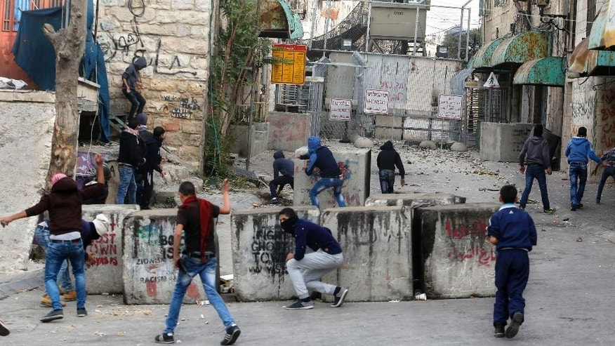 Palestinians hurl stones at Israeli troops during clashes following a protest in the West Bank city of Hebron, Wednesday, Nov 4, 2015. (AP Photo/Nasser Shiyoukhi)