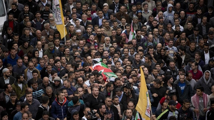 Palestinian mourners carry the body of Ibrahim Skafi, 22, during his funeral in the West Bank city of Hebron, Thursday, Nov. 5, 2015. Skafi rammed his vehicle into an Israeli police officer in the West Bank on Wednesday, seriously injuring him before he was shot and killed, police said. (AP Photo/Majdi Mohammed)