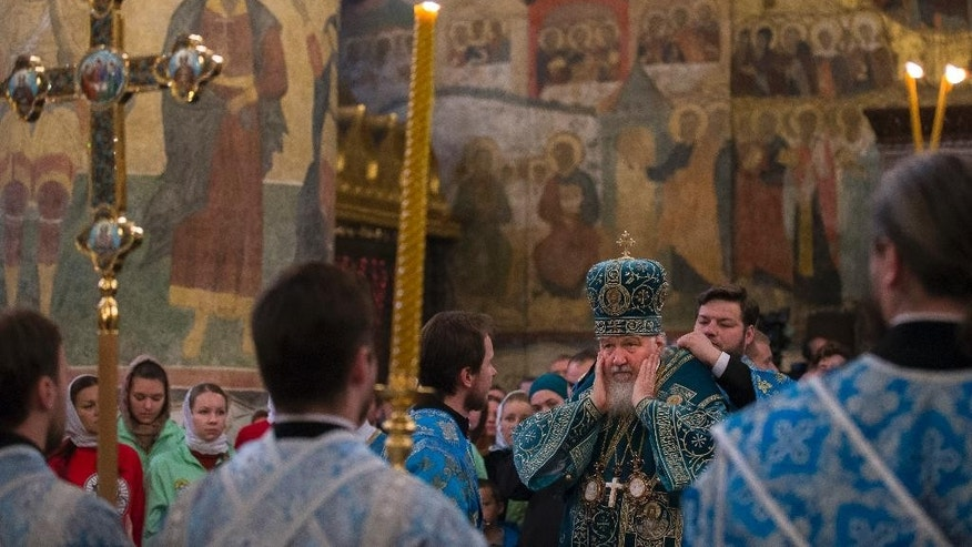 Russia's Patriarch Kirill prepares to conduct a religion service marking People's Unity Day inside the Cathedral of the Assumption, Cathedral Square in the Kremlin in Moscow, Wednesday, Nov. 4, 2015. The celebrations were scrapped in St. Petersburg as Russia's second-largest city mourns the victims of Saturday's plane crash in Egypt that killed 224 people. Authorities in Moscow, however, went ahead with the rally, which culminated in a pop concert on a central street.  (AP Photo/Alexander Zemlianichenko)