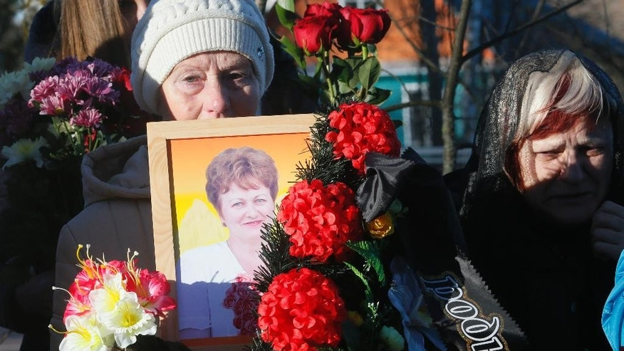 A woman holds a portrait of Nina Lushchenko, one of the victims of a plane crash,  during her funeral at a cemetery in the village of Sitnya, 80 km (about 50 miles) of Veliky Novgorod, Russia, Thursday, Nov. 5, 2015.  The first victim of Saturday's plane crash in Egypt was laid to rest on Thursday following a funeral service in a medieval church in the north Russian city of Veliky Novgorod.  Russia's Airbus 321-200 broke up over the Sinai Peninsula en route from the resort town of Sharm el-Sheikh to St. Petersburg, killing all 224 on board. (AP Photo/Dmitry Lovetsky)