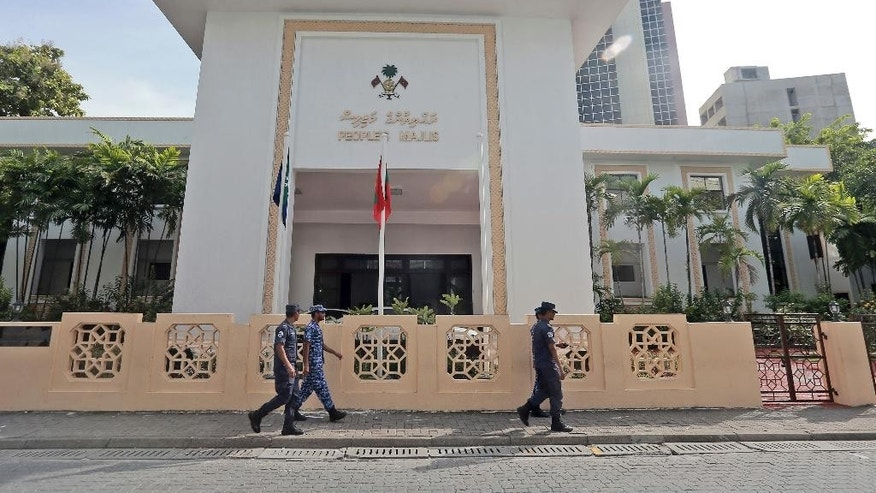 Policemen patrol near the Parliament building as members vote on the impeachment motion against Vice-President Ahmed Adeeb in Male, Maldives, Thursday, Nov. 5, 2015. Maldives' Parliament Thursday voted overwhelmingly to impeach the country's vice president, who has been accused of plotting to kill the president. (AP Photo/Sinan Hussain)