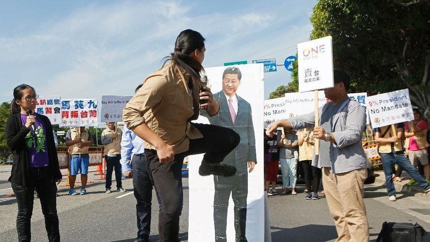 A protester kicks a portrait of China's President Xi Jinping outside of the Presidential Office as Taiwan's President Ma Ying-jeou holds a press conference inside about his upcoming Saturday meeting with Xi in Taipei, Taiwan, Thursday, Nov. 5, 2015. During the press conference Ma explained that he hopes this weekend's historic meeting in Singapore with China's leader Xi can ease Beijing's hard-line stance on diplomatic relations with Taiwan, which is now recognized by just 22 countries. (AP Photo/Anthony Chang)