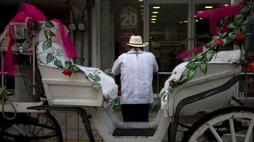 A tourist horse cart driver waits for customers outside the Yucatan State Government Palace, where Mexico's President Enrique Pena Nieto will meet Friday with Cuba's President Raul Castro, in Merida, Mexico, Thursday, Nov. 5, 2015. Mexicans are looking to increase trade with Cuba as the Cuban president makes his first state visit to Mexico, and the first such trip since relations between the two countries went cold in the early 2000s. (AP Photo/Rebecca Blackwell)