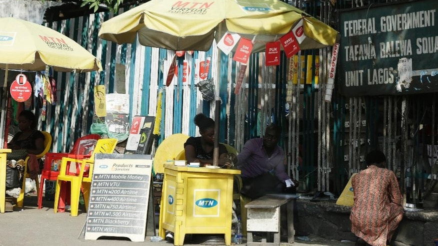 People sell MTN phone cards on a street in Lagos, Nigeria Thursday, Nov. 5, 2015. Africa's biggest telecommunications company is locked in a nasty battle with one of the most powerful governments on the continent, with billions of dollars at stake. MTN Nigeria, MTN Group's subsidiary here, was fined $5.2 billion for failing to meet an August deadline to deactivate 5.2 million unregistered cellphone SIM cards. (AP Photo/ Sunday Alamba)