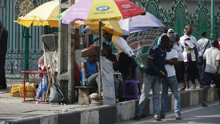 People buy MTN accessories on a street in Lagos, Nigeria Thursday, Nov. 5, 2015. Africa's biggest telecommunications company is locked in a nasty battle with one of the most powerful governments on the continent, with billions of dollars at stake. MTN Nigeria, MTN Group's subsidiary here, was fined $5.2 billion for failing to meet an August deadline to deactivate 5.2 million unregistered cellphone SIM cards. (AP Photo/Sunday Alamba)