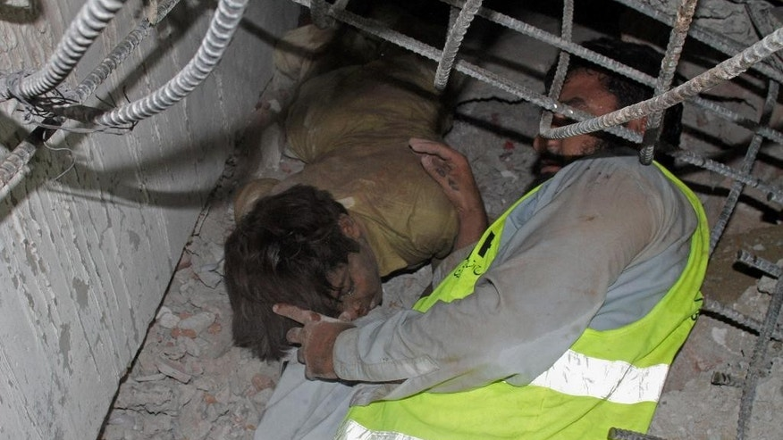 A Pakistani volunteer tries to rescue a trapped man following the collapse of a building in Lahore, Pakistan, Wednesday, Nov. 4, 2015. The factory building under construction in an industrial area on the outskirts of Pakistan's eastern city of Lahore collapsed on Wednesday, killing many workers and injuring dozens, officials said. (AP Photo/K.M. Chaudary)