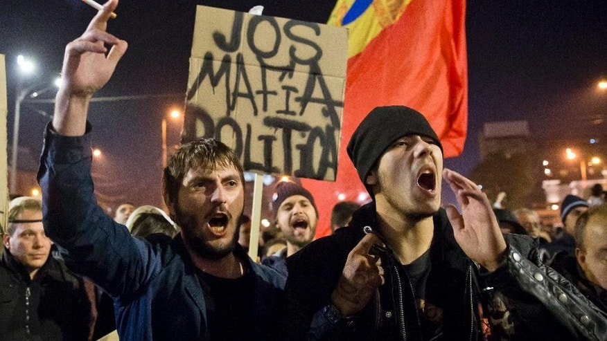 "Protesters shout slogans calling for early elections and hold banners that read: ""Down the Political Mafia"" after a rally joined by thousands blocked traffic in University Square in Bucharest, Romania, Wednesday, Nov. 4, 2015. Prime Minister Victor Ponta announced the resignation of his government Wednesday following huge protests the day before in the wake of a nightclub fire that killed more than 30 people. (AP Photo/Vadim Ghirda)"