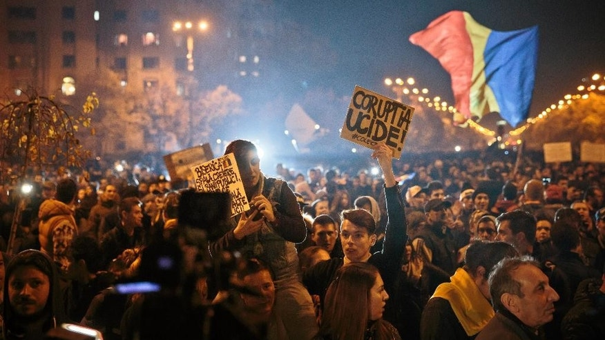 "Protesters hold banners reading ""Corruption kills"" and ""The Church washes brains and launders public money"" during a rally joined by thirty-five thousand people, according to local media quoting the Romanian Gendarmerie, calling for early elections, in Bucharest, Romania, Wednesday, Nov. 4, 2015. Prime Minister Victor Ponta announced the resignation of his government Wednesday following huge protests the day before in the wake of a nightclub fire that killed more than 30 people. (AP Photo/Vadim Ghirda)"
