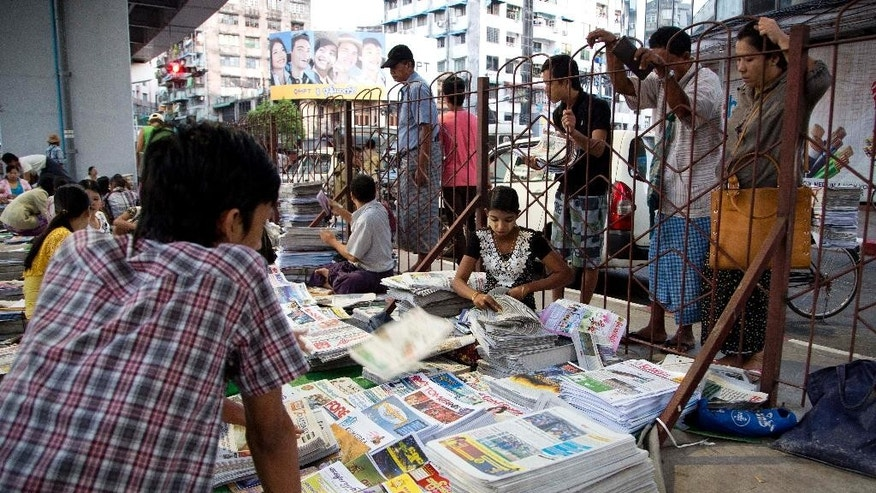 In this Tuesday Nov. 3, 2015 photo newspaper vendors collect papers for distribution in Yangon, Myanmar, Tuesday, Nov. 3, 2015. Their predecessors suffered torture, imprisonment and death at the hands of a die-hard military regime for more than half a century. Now, Myanmar's journalists, newly fledged, muscle-flexing but also still apprehensive are challenged with the first general election since 1960 to be covered with relative freedom.(AP Photo/Mark Baker)