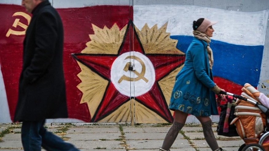 In this photo taken on Tuesday, Oct.  27, 2015, people pass by the Soviet Union's flag and symbol center, and a Russian flag, right, painted on the gate of a TV company in Luhansk, eastern Ukraine. The fighting has subsided, but Donetsk is quickly sinking into the past, a shabby Soviet-like state of empty streets and deprivation. Huge portraits of Josef Stalin hanging in the city center only reinforce the impression of failure.  (AP Photo/Max Black)
