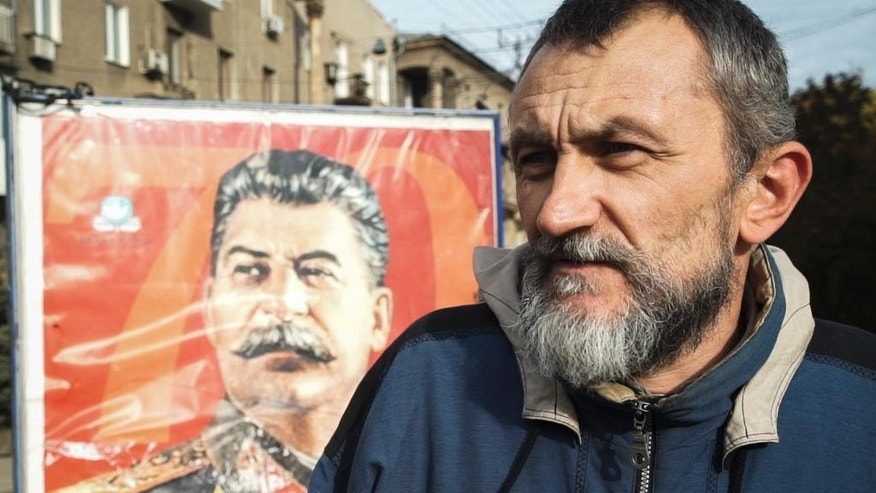 In this photo taken on Thursday, Oct.  22, 2015, Vadim Medchenko, an unemployed Donetsk resident, stands in front of a portrait of Soviet dictator Josef Stalin during  an interview in downtown Donetsk, eastern Ukraine. The fighting has subsided, but Donetsk is quickly sinking into the past, a shabby Soviet-like state of empty streets and deprivation. Huge portraits of Josef Stalin hanging in the city center only reinforce the impression of failure. (AP Photo/Max Black)