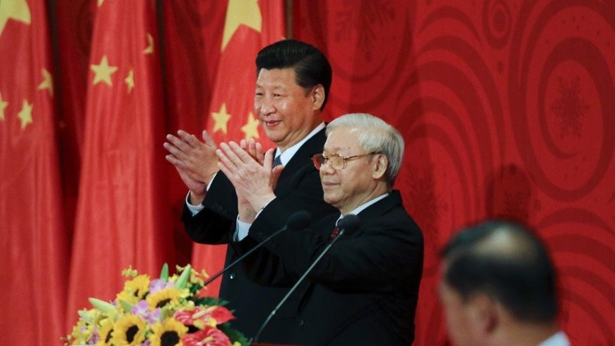 Chinese President Xi Jinping, left, and Vietnamese Communist Party General Secretary Nguyen Phu Trong clap hands at a meeting with Vietnamese and Chinese communist youths in Hanoi, Vietnam, Friday, Nov. 6, 2015. (AP Photo/Na Son Nguyen, Pool)