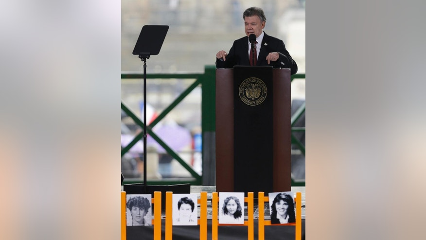 Colombia's President Juan Manuel Santos speaks on the 30th anniversary of a deadly government siege at the rebuilt Palace of Justice in Bogota, Colombia, Friday, Nov. 6, 2015, behind photos of Supreme Court workers who disappeared during the attack. Santos apologized for his country's actions during a 1985 army raid on the Supreme Court, acting in accordance with a ruling last year by the Inter-American Court of Human Rights condemning the state for the disappearance of 12 individuals, mostly cafeteria workers, who were taken alive from the building during the 48-hour standoff. (AP Photo/Fernando Vergara)