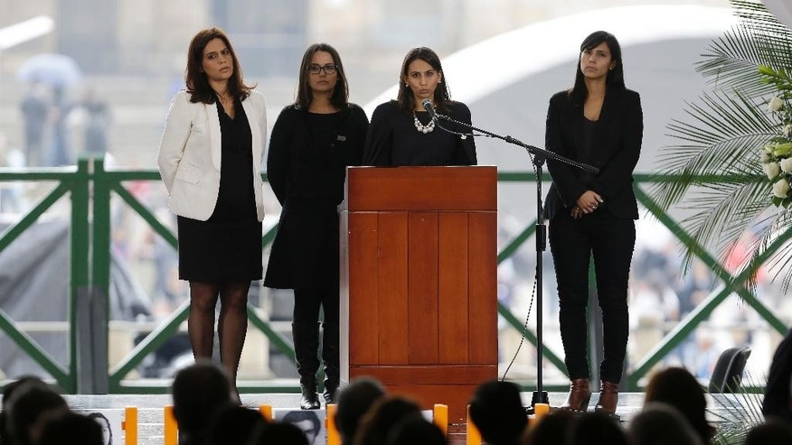 Daughters of the late judge Carlos Uran address people attending a ceremony commemorating the 30th anniversary of a deadly government siege, at the rebuilt Palace of Justice in Bogota, Colombia, Friday, Nov. 6, 2015. Colombian President Juan Manuel Santos apologized for his country's actions during a 1985 army raid on the Supreme Court, acting in accordance with a ruling last year by the Inter-American Court of Human Rights condemning the state for the disappearance of 12 individuals, mostly cafeteria workers, who were taken alive from the building during the 48-hour standoff. (AP Photo/Fernando Vergara)
