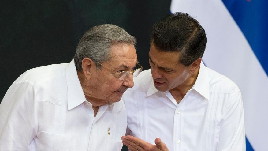 Mexican President Enrique Pena Nieto, right, talks with Cuba's President Raul Castro during an official welcome ceremony at the Yucatan state government palace in Merida, Mexico, Friday, Nov. 6, 2015. Castro has arrived for his first state visit to Mexico to review a relationship between longtime allies that grew chilly at the beginning of the century. (AP Photo/Rebecca Blackwell)