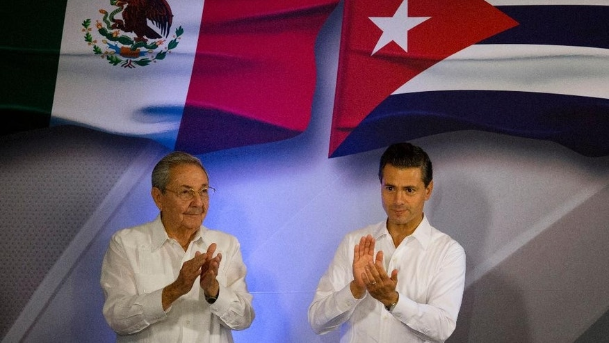 "Mexican President Enrique Pena Nieto, right, and Cuban President Raul Castro applaud during the signing of bilateral agreements, at the Yucatan State Government Palace in Merida, Mexico, Friday, Nov. 6, 2015. The presidents announced agreements to fight human trafficking and exchanges in tourism, education and business designed to increase Mexican investment in Cuba, as well as ""a dialogue at the highest political levels."" (AP Photo/Rebecca Blackwell)"