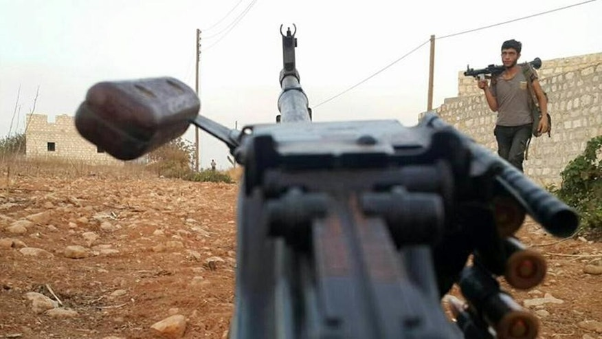 In this photo released on October 17, 2015, and provided by the Fursan al-Haq Syrian rebel brigade, which has been authenticated based on its contents and other AP reporting, a Free Syrian Army fighter of Fursan al-Haq brigade holds his weapon, in Azzan village, in the countryside of Aleppo province, Syria. Despite a month of heavy battering by Russian airstrikes, Syria's rebels have so far been able to fend off offensives by government forces trying to retake territory from the rebel's heartland. The fierce fighting shows how even greater backing from Syrian President Bashar Assad's international allies is not swiftly tipping the conflict in his favor.(Fursan al-haq Rebel Brigade via AP)