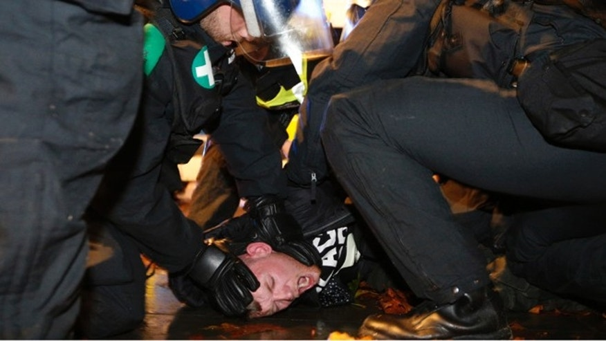 Nov. 5, 2015: A supporter of the activist group Anonymous is detained by police officers during a protest in London, Britain.