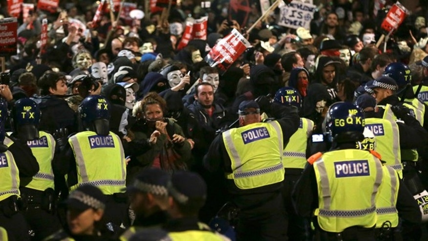 Nov. 5, 2015: Police try and block masked demonstrators as they march in central London during the Million Mask protest march.