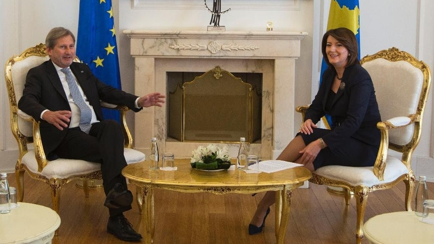 Kosovo President Atifete Jahjaga, right, meets EU Commissioner for European Neighbourhood Policy & Enlargement Negotiations Johannes Hahn, left, in capital Pristina on Friday, Nov. 6, 2015. Hahn has warned Kosovo opposition members that blocking Parliament will hamper the country's further integration into the 28-nation bloc. (AP Photo/Visar Kryeziu)
