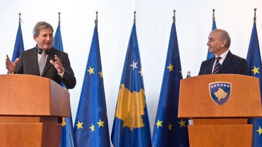 Kosovo Prime Minister Isa Mustafa, right, looks at EU Commissioner for European Neighbourhood Policy & Enlargement Negotiations Johannes Hahn, left, during a joint press conference in capital Pristina on Friday, Nov. 6, 2015. Hahn has warned Kosovo opposition members that blocking Parliament will hamper the country's further integration into the 28-nation bloc. (AP Photo/Visar Kryeziu)