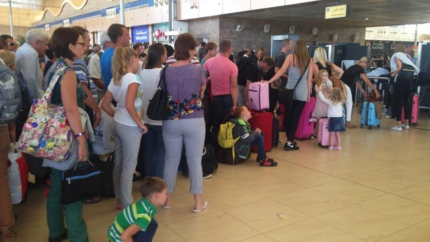 Tourists wait in line at the security gate before the check-in counter at Sharm el-Sheikh International Airport, south Sinai, Egypt, Friday, Nov. 6, 2015. Egypt police are carrying out detailed security checks around the airport at Sharm el-Sheikh, the resort from where the doomed Russian plane took off last weekend, after U.K. officials confirmed that flights will start bringing stranded British tourists home from the Sinai Peninsula. (AP Photo/Thomas Hartwell)