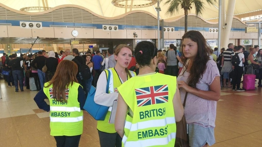 A tourist talks to staff from the British Embassy as other tourists wait in line at the security gate before the check-in counter at Sharm el-Sheikh International Airport, south Sinai, Egypt, Friday, Nov. 6, 2015. Egypt police are carrying out detailed security checks around the airport at Sharm el-Sheikh, the resort from where the doomed Russian plane took off last weekend, after U.K. officials confirmed that flights will start bringing stranded British tourists home from the Sinai Peninsula. (AP Photo/Thomas Hartwell)