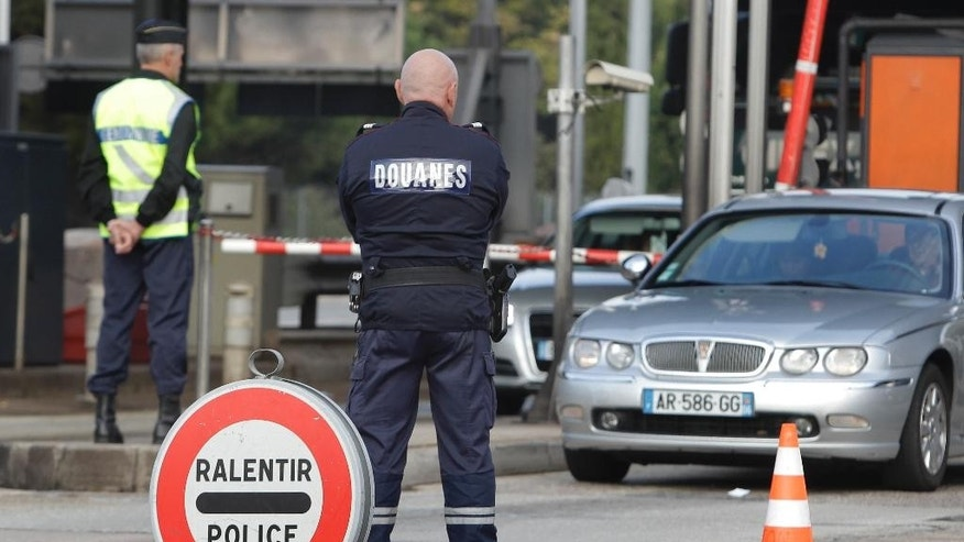 FILE - In this Monday, Oct. 31, 2011 file photo, a French gendarme and French custom officer check vehicles, in La Turbie, southeastern France, near the Franco-Italian border, in spite of the EU's passport-free zone Schengen, as security measures are taken ahead of the G20 Summit of Cannes. France will reinstate controls on its borders — normally open to other countries in Europe's free-travel zone — for the period around a major U.N. climate conference in Paris, the interior minister said Friday, Nov. 6, 2015. (AP Photo/Lionel Cironneau, File)