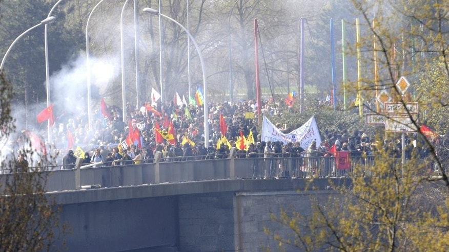 FILE - In this April 4, 2009 file photo, smoke is rising  on the bridge of Europe in Kehl, southern Germany and leading to France, while French anti NATO  demonstrators and police stand face to face. France will reinstate controls on its borders _ normally open to other countries in Europe's free-travel zone _ for the period around a major U.N. climate conference in Paris, the interior minister said Friday Nov.6, 2015. Authorities are on alert for violent protesters as well as potential terror attacks around the Nov. 30-Dec. 11 conference. (AP Photo/Winfried Rothermel, File)