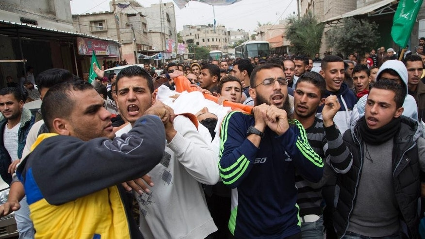 Palestinian mourners chant Islamic slogans while carrying the body of fisherman Faris Meqdad, 18, during his funeral in Rafah, Gaza Strip, Friday, Nov. 6, 2015. Palestinian Health Ministry spokesman Ashraf al-Kidra says the 18-year-old fisherman was shot in the abdomen and died after being brought to a hospital. Palestinian officials say a fisherman was shot and killed by Egyptian naval forces off the Gaza coast on Thursday. (AP Photo/Adel Hana)
