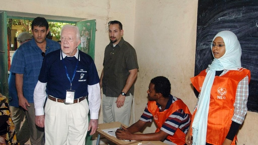 FILE - In this April 11, 2010 file photo, former U.S. President Jimmy Carter, front left, observes a polling station for Sudan's first multiparty elections in decades in Khartoum. Afflicted by cancer, former President Jimmy Carter won't be present for Myanmar's watershed election Sunday. But the center founded will, monitoring a vote in a crisis-ridden corner of the world for the 101st time to ensure polling is free and credible. (AP Photo/Abd Raouf, File)