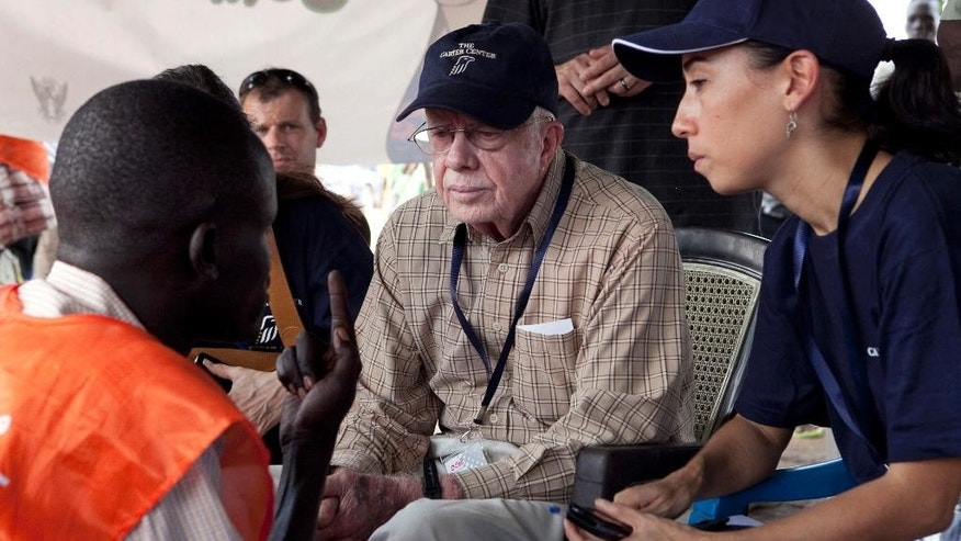 FILE - In this April 13, 2010 file photo, former U.S. President Jimmy Carter, center, speaks with a polling official at a polling station outside Juba, southern Sudan. Afflicted by cancer, former President Jimmy Carter won't be present for Myanmar's watershed election Sunday. But the center founded will, monitoring a vote in a crisis-ridden corner of the world for the 101st time to ensure polling is free and credible. (AP Photo/Pete Muller, File)