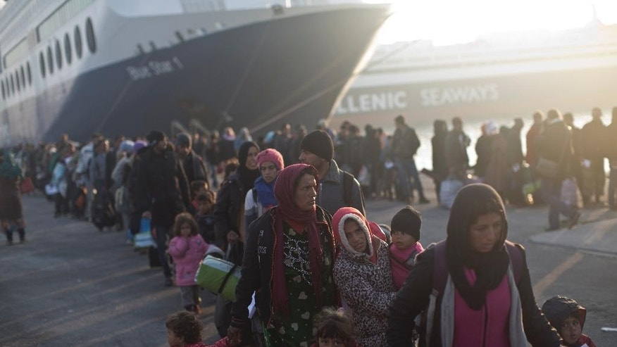 People queue in order to board a ferry at the port of Mytilene on the island of Lesbos, Greece, Friday, Nov. 6, 2015. Thousands of migrants and refugees were allowed to board vessels in Mytilene on Friday, as Greek ferries ended a strike that had left them trapped on eastern Aegean islands. (AP Photo/Marko Drobnjakovic)
