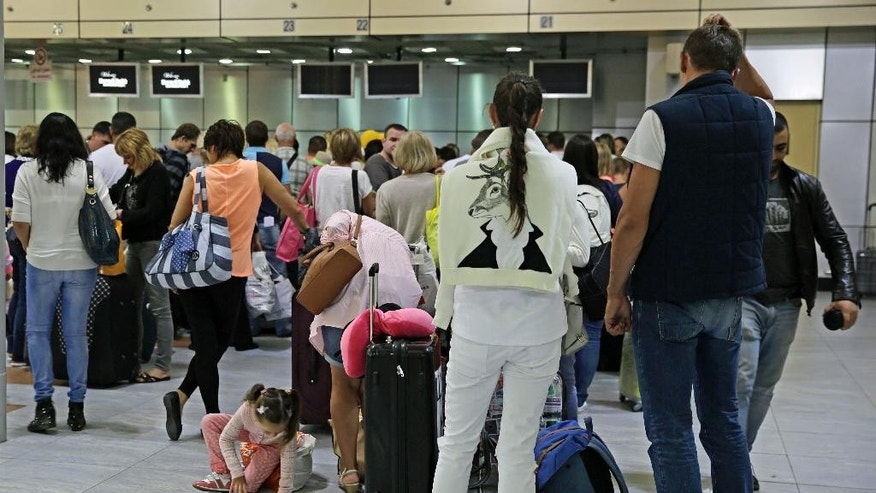 Russian tourists check in as they prepare to depart for St.Petersburg, Russia from Sharm el-Sheikh International Airport, south Sinai, Egypt, Thursday, Nov. 5, 2015.  Five days after a Russian jetliner broke apart high above the Sinai, Russia and Egypt on Thursday dismissed Western suggestions that a terrorist bomb may have caused the crash that killed 224 people, saying the speculation was a rush to judgment. (AP Photo/Thomas Hartwell)