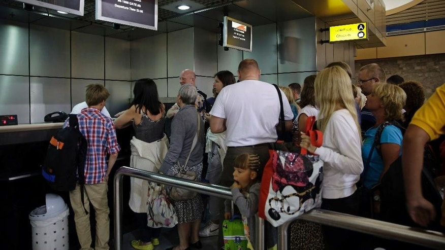 Russian tourists check in to depart for St.Petersburg, Russia from Sharm el-Sheikh International Airport, south Sinai, Egypt, Thursday, Nov. 5, 2015.  Five days after a Russian jetliner broke apart high above the Sinai, Russia and Egypt on Thursday dismissed Western suggestions that a terrorist bomb may have caused the crash that killed 224 people, saying the speculation was a rush to judgment. (AP Photo/Thomas Hartwell)