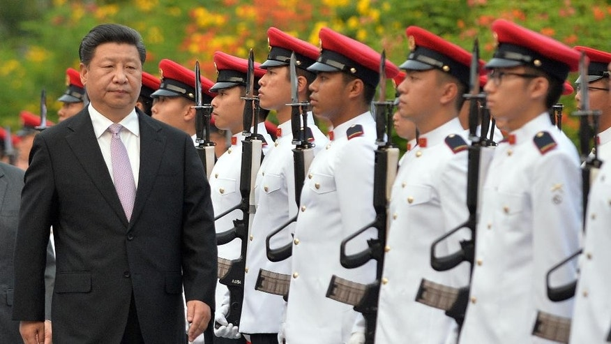 Chinese President Xi Jinping reviews the guard of honor at a welcoming ceremony at the Istana in Singapore, Friday, Nov. 6, 2015. Xi is scheduled to meet with Taiwan's President Ma Ying-jeou in Singapore on Saturday. (Mohd Fyrol/Pool Photo via AP)