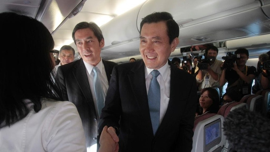 Taiwan's President Ma Ying-jeou, center, greets journalists accompanying him on his flight from Taiwan to Singapore for a meeting with China's President Xi Jinping, Saturday, Nov. 7, 2015. Taiwan's Ma and China's Xi are the first leaders from the two sides to meet since their territories split during the Chinese civil war in 1949. Ma is the successor to Chiang Kai-shek, whose Nationalists retreated to the island, while Xi now leads Mao Zedong's victorious Communists, who set up government in Beijing. (AP Photo/Chiang Ying-ying)