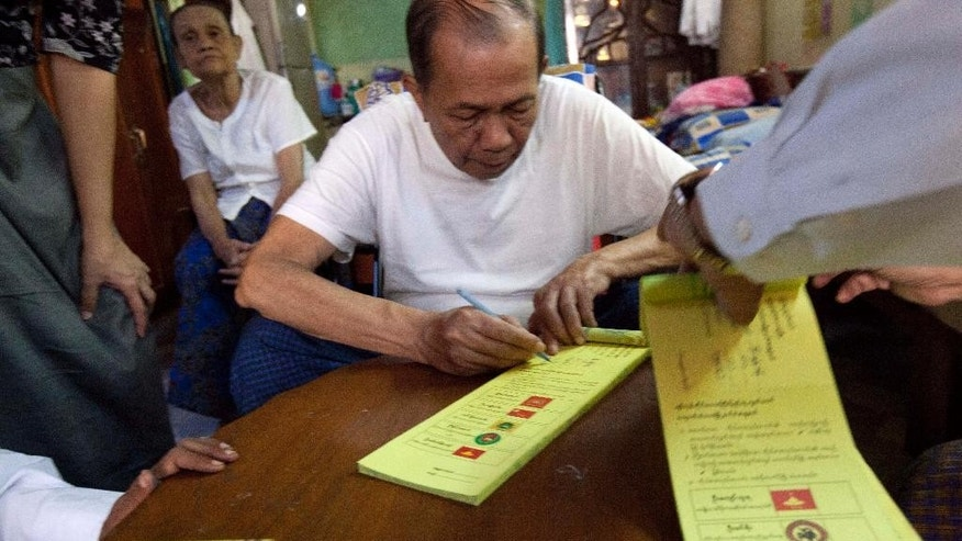 A man signs to get ballot from election commission officers to cast his early vote at his residence Friday, Nov 6, 2015, in Yangon, Myanmar. Myanmar's general elections are scheduled for Nov. 8, the first since a nominally civilian government was installed in 2011. (AP Photo/Khin Maung Win)