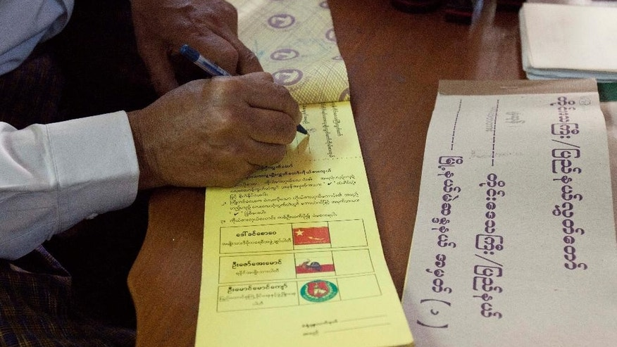 An election commission officer signs on a ballot to give it to a voter to cast early vote at a house Friday, Nov. 6, 2015, in Yangon, Myanmar. Myanmar's general elections are scheduled for Nov. 8, the first since a nominally civilian government was installed in 2011. (AP Photo/Khin Maung Win)