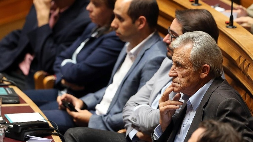 In this Oct. 23 2015 photo, Jeronimo de Sousa, right, leader of the Portuguese Communist Party, attends the first session of the post-election Parliament, in Lisbon. Die-hard communists are poised to walk the corridors of power in Portugal, and a new generation of leftist radicals is right beside them. The Portuguese Communist Party and the radical Left Bloc say they are hitching up with the bigger, moderate Socialist Party for what will likely be a successful _ and controversial _ gambit next week to unseat the country's center-right government just days after it was sworn in. The three parties then intend to take command of the country's fortunes for the next four years in a bold power play that just a few weeks ago was unthinkable. (AP Photo/Armando Franca)