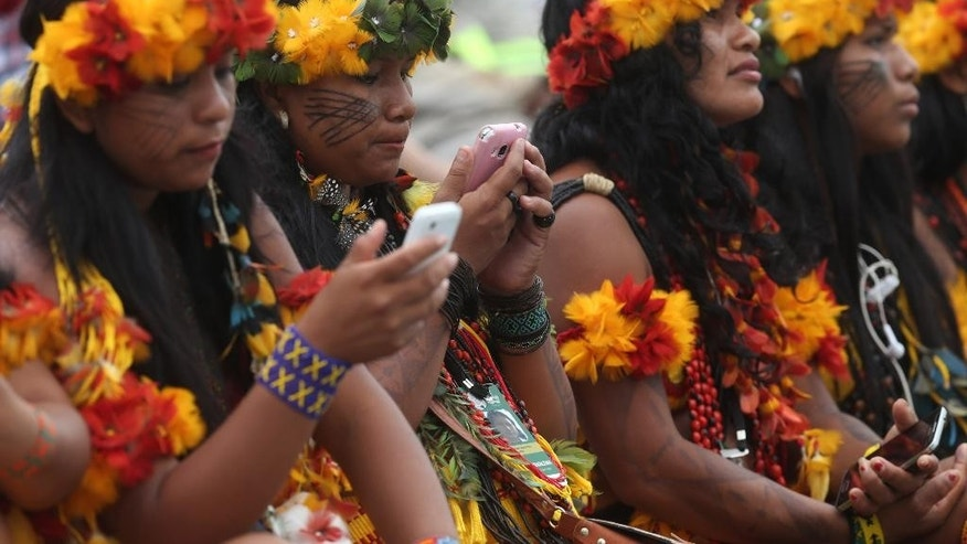 In this Oct. 23, 2015 photo, Brazilian Paresi indigenous women use their cell phones during the World Indigenous Games in Palmas, Brazil. Experts warn that 40 percent of Brazil's remaining indigenous languages could be lost in the next few decades, as elders die off and young people get more access to television, the Internet and cell phones. (AP Photos/Eraldo Peres)