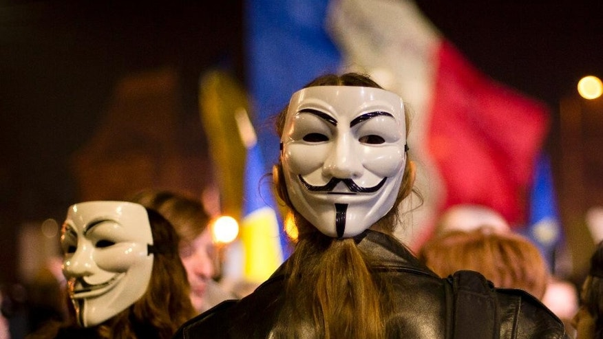 People wear Guy Fawkes masks during the third day of protests, joined by tens of thousands across the country, calling for early elections, in Bucharest, Romania, Thursday, Nov. 5, 2015. Romania's President Klaus Iohannis has named the education minister Sorin Campeanu as interim premier following the resignation of the prime minister Victor Ponta and his cabinet. (AP Photo/Vadim Ghirda)