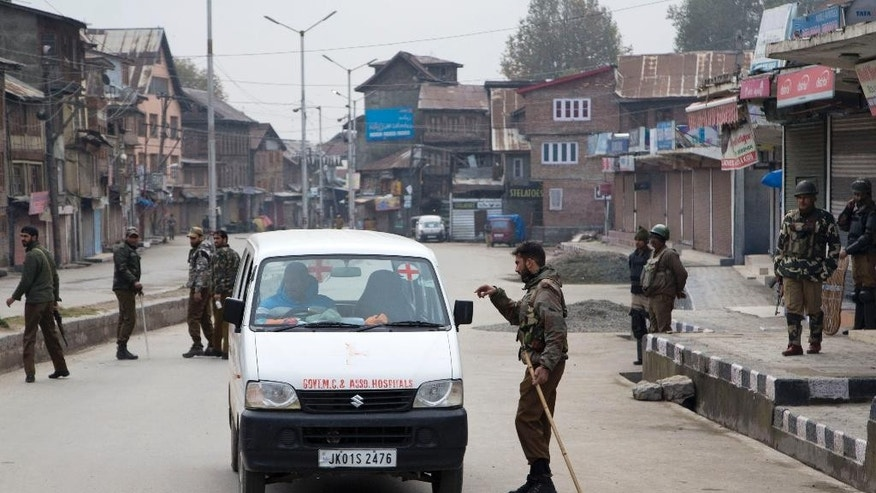 An Indian policeman questions an ambulance driver at a temporary checkpoint during restrictions in Srinagar, Indian controlled Kashmir, Friday, Nov. 6, 2015. Authorities imposed curfew in some parts of Himalayan Kashmir on Friday as government forces swept through the disputed region to stop anti-India protests ahead of the Indian prime minister's visit. (AP Photo/Dar Yasin)