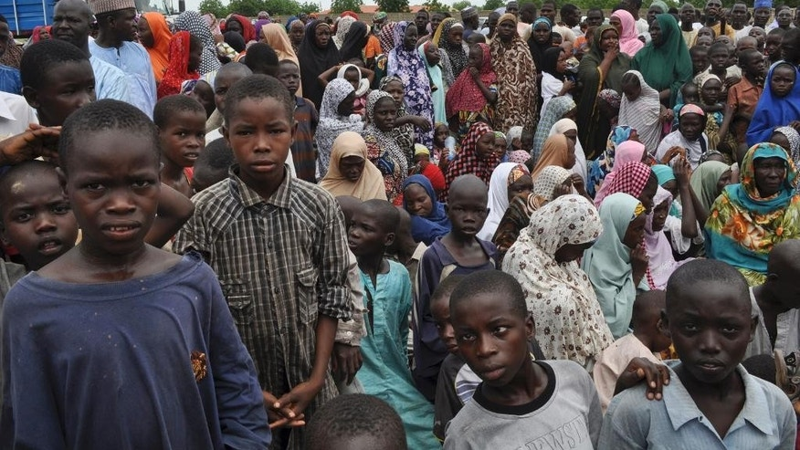FILE - In this Tuesday Sept. 9, 2014 file photo, civilians who fled their homes following an attack by Islamist militants in Bama, take refuge at a school in Maiduguri, Nigeria. A new refugee camp with 2,500 temporary homes is being built in Nigeria's northeastern city of Maiduguri, and must be built by the end of Nov. 2015, for some of the million-plus refugees there from the Boko Haram uprising giving another sign that few expect the conflict to end soon. (AP Photo/Jossy Ola, File)