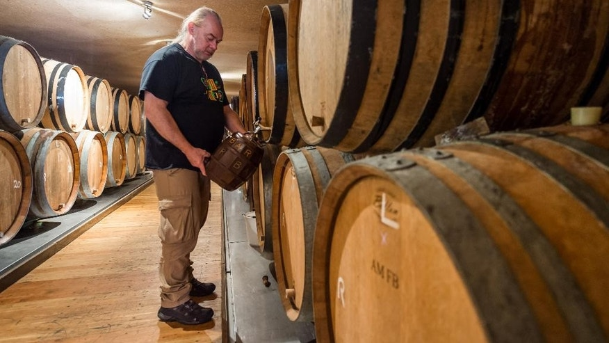 A worker takes a sample out of a barrel in the Cantillon gueuze brewery in Brussels, Friday Nov. 6, 2015. One of the most renowned Belgian beer brewers says it is a victim of climate change because increasingly high temperatures shortened the brewing season by a month since the 1950s. The Cantillon gueuze brewery needs to cool its hot brew in open vessels so that the natural yeasts in the air can help produce the sour beer that has developed a niche following throughout the world. (AP Photo/Geert Vanden Wijngaert)