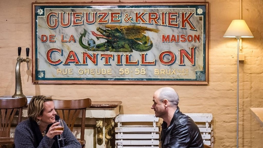 Visitors drink a gueuze beer in the Cantillon gueuze brewery in Brussels, Friday Nov. 6, 2015. One of the most renowned Belgian beer brewers says it is a victim of climate change because increasingly high temperatures shortened the brewing season by a month since the 1950s. The Cantillon gueuze brewery needs to cool its hot brew in open vessels so that the natural yeasts in the air can help produce the sour beer that has developed a niche following throughout the world. (AP Photo/Geert Vanden Wijngaert)