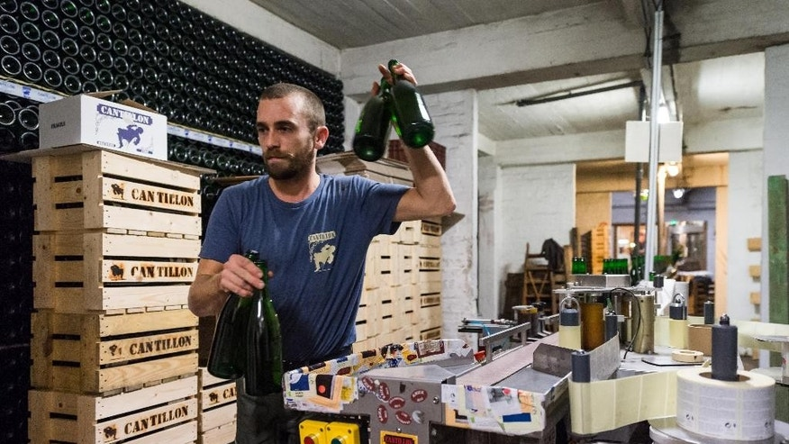 A worker takes bottles from the bottling line in the Cantillon gueuze brewery in Brussels, Friday Nov. 6, 2015. One of the most renowned Belgian beer brewers says it is a victim of climate change because increasingly high temperatures shortened the brewing season by a month since the 1950s. The Cantillon gueuze brewery needs to cool its hot brew in open vessels so that the natural yeasts in the air can help produce the sour beer that has developed a niche following throughout the world. (AP Photo/Geert Vanden Wijngaert)
